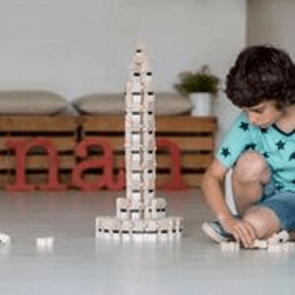 Speelgoedwinkel Daantje El Nan jongen speelt met houten naturel stapel poppetjes